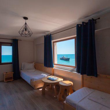 BlackSeaView - Camere - Apartament - paturi sofa, fereastră cu detaliu epavă